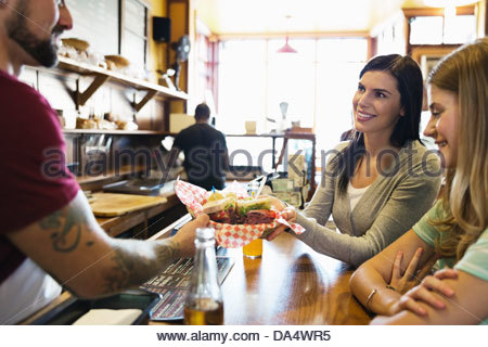Male deli owner serving food to customers at counter - Stock Photo