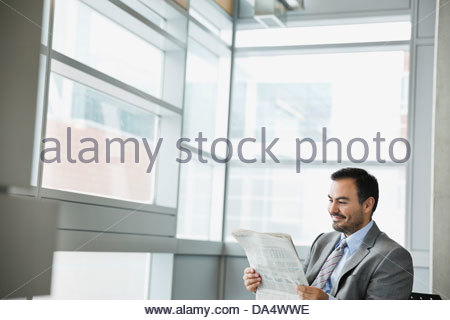 Businessman reading newspaper in office building - Stock Photo