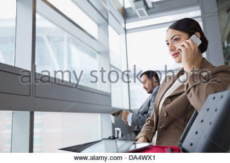 Businesswoman with mobile phone sitting in airport - Stock Photo