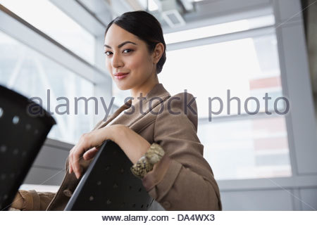 Portrait of businesswoman sitting on chair in airport - Stock Photo