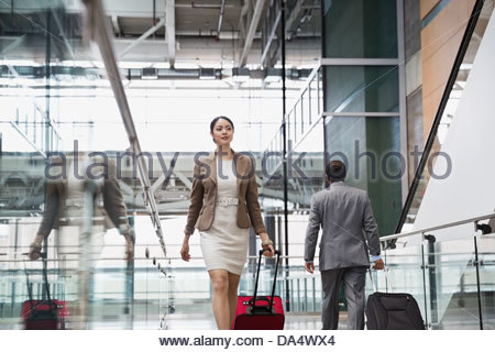 Businesswoman with suitcase walking at airport - Stock Photo