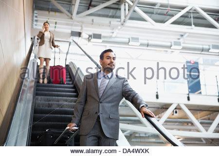 Businessman on escalator in airport - Stock Photo