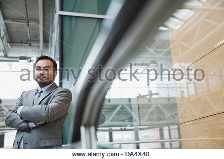 Portrait of businessman standing in office building - Stock Photo