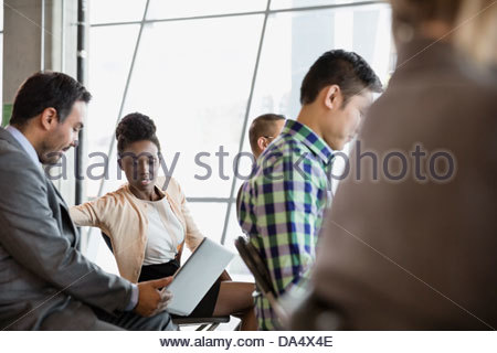 Man and woman looking at laptop in business meeting - Stock Photo