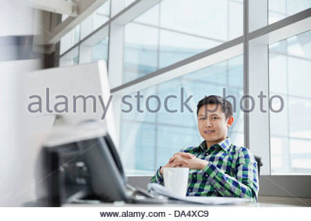 Portrait of businessman sitting at desk in office - Stock Photo