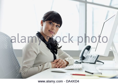 Portrait of businesswoman sitting at desk in office - Stock Photo
