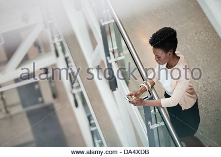 High angle view of woman using mobile phone in office building - Stock Photo