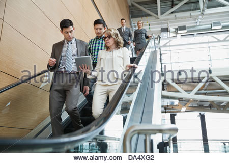 Business people using escalator in office building - Stock Photo