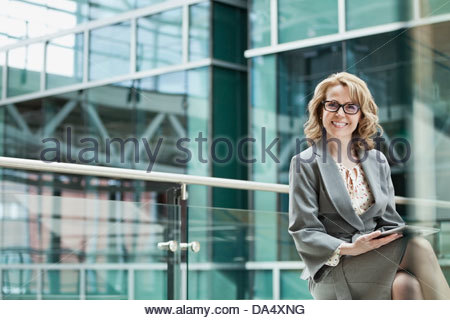 Portrait of businesswoman with digital tablet sitting in office building - Stock Photo