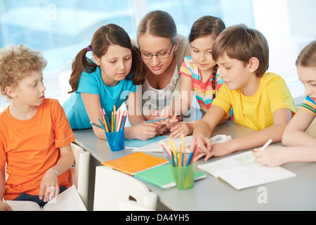 Portrait of diligent schoolkids and their teacher interacting at lesson - Stock Photo