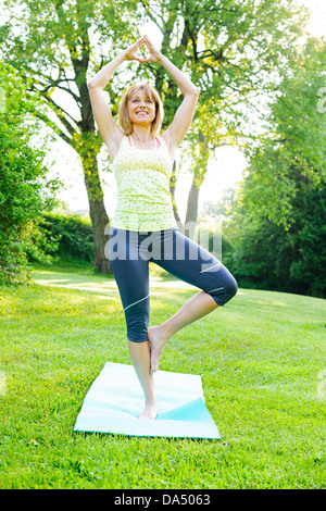 Female fitness instructor doing yoga tree or vrksasana pose in green park - Stock Photo