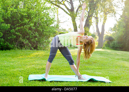 Female fitness instructor doing yoga extended triangle pose outdoors in green park - Stock Photo