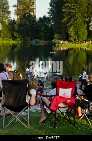 Crowds gather by LaFarge Lake in Coquitlam, BC for the annual Canada Day celebration and fireworks show. - Stock Photo