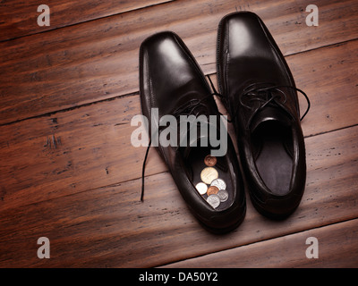 Closeup of mens shoes on the floor with change coins inside. Keeping or finding money in a wrong place, concept. - Stock Photo