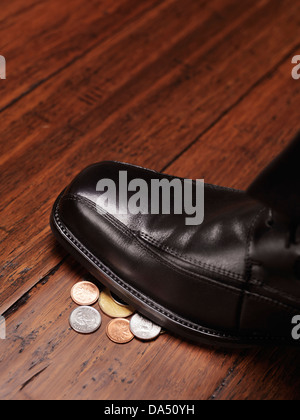 Closeup of a man shoe standing on change, coins, money found on the floor concept - Stock Photo