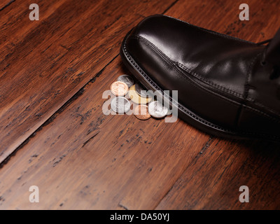 Finding money concept of a man shoe stepping on change coins on the floor. - Stock Photo