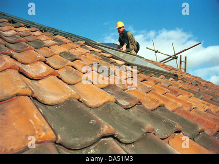 Roofer installing solar panel on roof in Hackney UK - Stock Photo