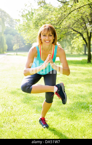 Smiling female fitness instructor doing yoga tree pose in green park - Stock Photo
