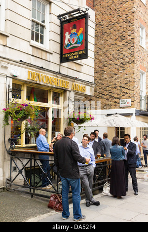 Patrons Enjoying a Drink Outside at the Devonshire Arms, London - Stock Photo