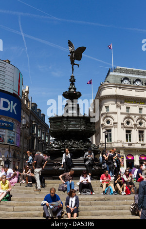 Piccadilly Circus, people enjoying the sun under the statue of Eros, Londons West End, London, Engtand, UK - Stock Photo