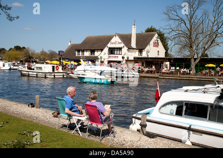A couple on summer holiday sitting on the banks of the River Bure opposite the Ferry Inn, Horning, Norfolk Broads, - Stock Photo