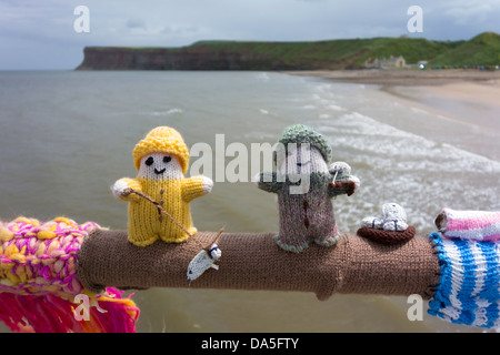 Yarn Bombing decorating public place with knitted objects here a small people fishing - Stock Photo