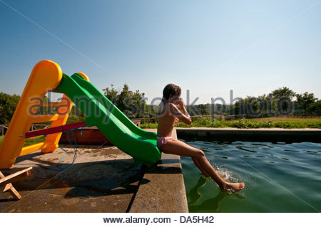 girl in the pool on a slide - Stock Photo