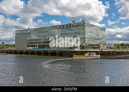 Cruise vessel Rover approaches the berth by BBC Scotland headquarters building at Pacific Quay on the River Clyde - Stock Photo