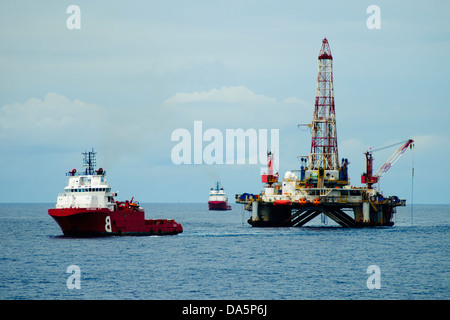 Supply vessel close to an offshore oil rig at campos basin, brazil - Stock Photo
