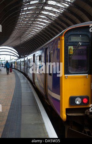 Commuters waiting for rail transport on platform at main-line railway station in the city of York, Yorkshire, England, - Stock Photo