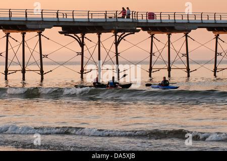Colourful summer sunset sky & view of people walking on seaside pier & 3 men in kayaks kayaking in sea by seashore - Stock Photo