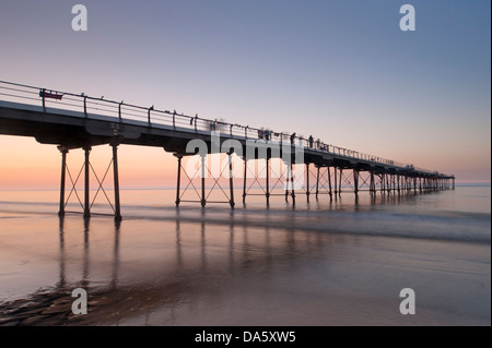 Under colourful summer sunset sky, view from sandy beach of people walking on historic seaside pier over calm sea - Stock Photo