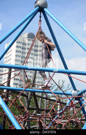 A five year old girl at the top of a climbing frame in an adventure playground in an urban park - Stock Photo