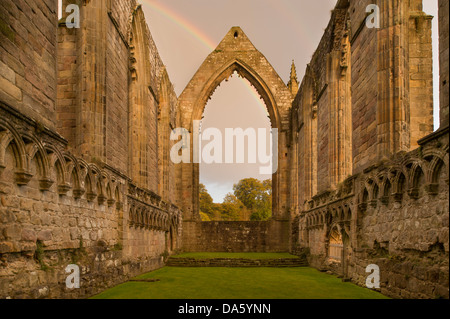 View of sunlit, ancient, picturesque monastic ruins of Bolton Abbey with rainbow in dark sky above east chancel - Stock Photo