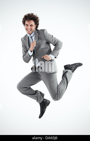 Young businessman excitedly jumps into the air in celebration. Vertical shot. Looking at camera. - Stock Photo