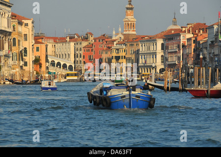 life on the Grand Canal in Venice with the Rialto bridge in the background, and palazzi on either side - Stock Photo