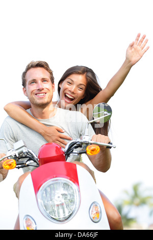 Young couple on scooter in love and happy together. Joyful mixed race couple having fun together outside driving - Stock Photo