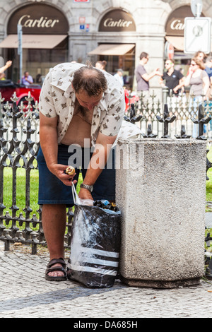 A homeless man looks through litter for food in Town Square, Prague. Cartier shop in background. Contrast of wealth - Stock Photo
