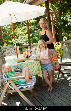 Mother and daughters (6-7) eating hot dogs in garden - Stock Photo