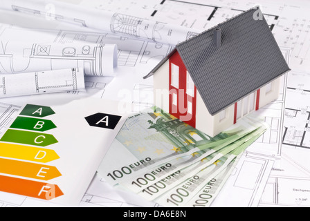 Energy efficiency label with architectural model, blueprints and bills. - Stock Photo