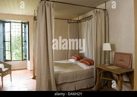 Cream drapes on metal four poster bed with striped cushion and cream linen in French country bedroom with lamp on - Stock Photo