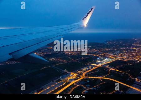 Plane flying at dusk over Santander Cantabria Spain - Stock Photo