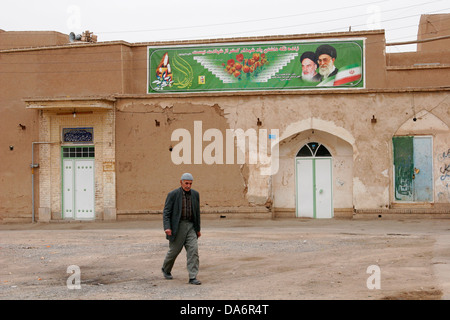 Muslim man walking on the street with billboard of Ayatollah Khameini and Khomeini,  Central Iran - Stock Photo