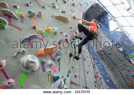 Low angle view of woman climbing on climbing wall at gym - Stock Photo