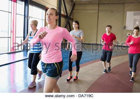 Woman jogging with class in fitness center - Stock Photo