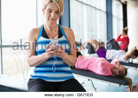 Woman listening to music on smartphone in fitness center - Stock Photo