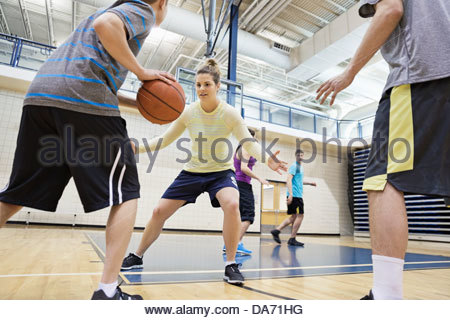 Men and women playing basketball in gym - Stock Photo