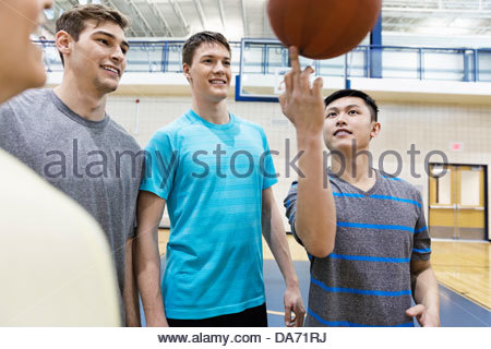 Man spinning basketball on finger in gym - Stock Photo