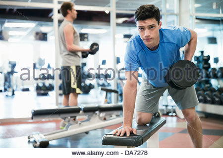 Man lifting weights in fitness center - Stock Photo