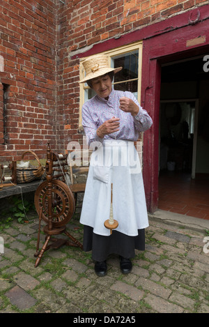 Shropshire. Acton Scott historic working farm. Victorian costumed woman Spinning on a Hand Spindle. England, UK - Stock Photo